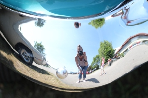 A selfie taken in the bumper of a shiny, classic 1950s car.