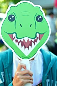A child holding a green dinosaur mask.