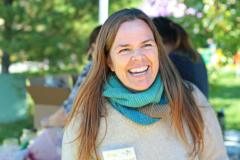 A woman with long hair smiling while volunteering at the Memorial Centre Farmer's Market in Kingston, Ontario.