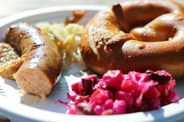 Sausage, pretzel, red cabbage on a plate for Oktoberfest. German meal.