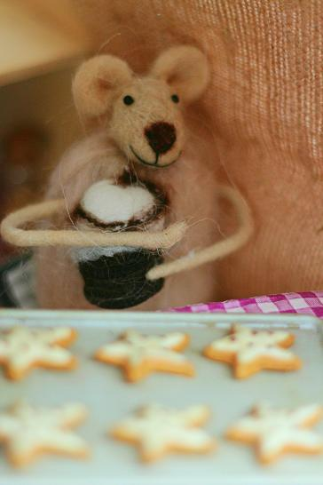 A felted mouse in a Christmas display, baking Christmas cookies.
