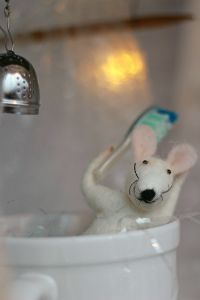 A wool felted mouse in a Christmas display, sitting in a cup, taking a shower.