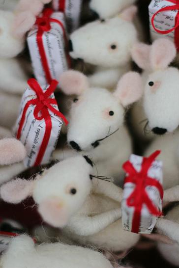A basket full of wool felted Christmas mice, holding festively wrapped Christmas gifts.