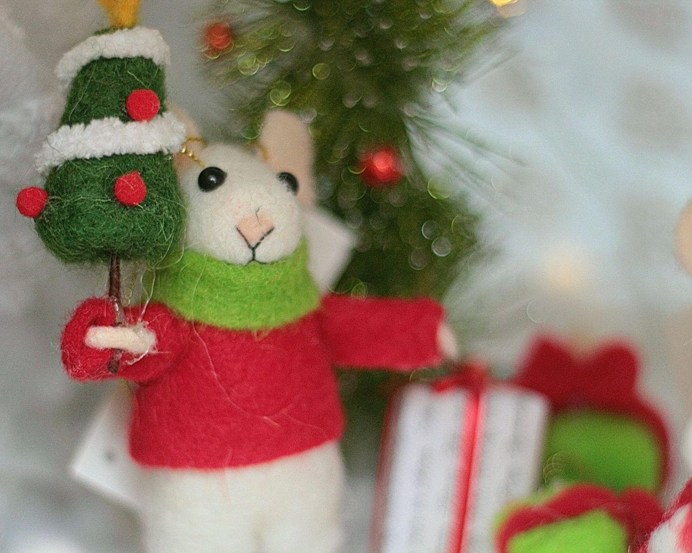 A felted wool mouse, festively dressed up in red & green for the season, holding a Christmas tree.