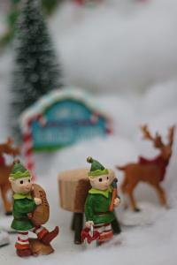 Little elves, reindeer in a snowy landscape in a Christmas display.